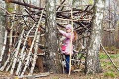 A menina constrói a cabana entre vidoeiros imagens de stock royalty free