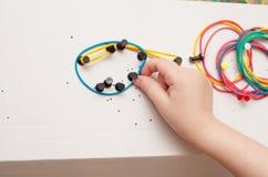 A menina constrói formas dos elásticos coloridos Fotos de Stock