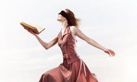 Menina contra o céu nebuloso com o livro aberto na palma como a ideia para o conhecimento imagem de stock