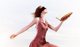 Menina contra o c?u nebuloso com o livro aberto na palma como a ideia para o conhecimento fotografia de stock royalty free