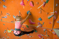 A menina é contratada na escalada Foto de Stock Royalty Free
