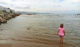 A menina cor-de-rosa e o mar foto de stock royalty free