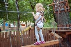 A menina corajoso pequena supera o obstáculo no parque da corda fotos de stock royalty free