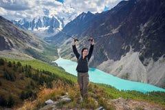 Menina corajoso que conquista picos de montanha das montanhas de Altai A natureza majestosa dos picos e dos lagos de montanha Cam Imagens de Stock Royalty Free