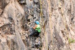Menina corajoso que escala uma parede da rocha Foto de Stock Royalty Free