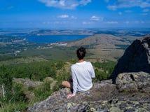 Menina corajoso que senta-se na borda da pedra enorme fotografia de stock