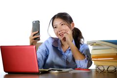 Menina coreana asiática bonita e feliz nova do estudante que estudam com pilha do livro e mesa do laptop que toma a imagem do sel imagem de stock royalty free