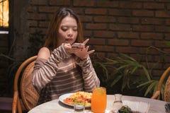 Menina coreana asiática bonita e feliz nova do estudante que senta-se na cafetaria doce que toma a foto de sua refeição com câmer imagem de stock royalty free