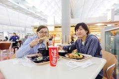 A menina coreana come o alimento japonês em Hong Kong International Airport Imagens de Stock