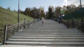 A menina corre acima das escadas O corredor corre acima das escadas Movimento lento vídeos de arquivo