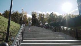 A menina corre acima das escadas O corredor corre acima das escadas Movimento lento As elevações da câmera video estoque