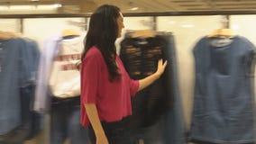 A menina corre ao longo de Windows na loja filme