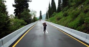 A menina corre no asfalto molhado O terreno montanhoso, os lados da estrada é abeto vermelho e grama verde filme