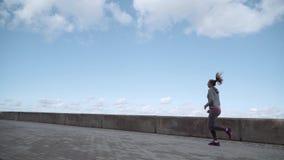 A menina corre no pavimento O louro está correndo ao longo da terraplenagem Corredor da manhã video estoque