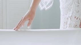 A menina corre uma mão bonita na borda de um banho neve-branco filme
