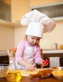 A menina corta a massa de pão para bolinhos na cozinha foto de stock