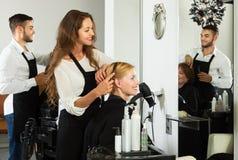 A menina corta o cabelo no cabeleireiro fotografia de stock