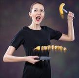 A menina corta uma banana. Fotos de Stock