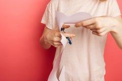 A menina cortou o papel, contratado no bordado, no fundo cor-de-rosa, anunciando fotografia de stock royalty free