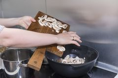 A menina cozinha o alimento, derrama os cogumelos da placa no foto de stock