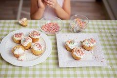 A menina cozinha os bolos pequenos da Páscoa está na tabela na cozinha imagem de stock
