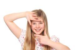 A menina cria um frame com seu dedo Fotografia de Stock Royalty Free