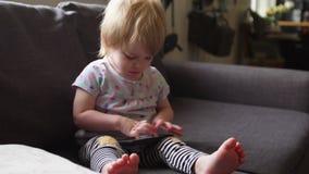 A menina criança brinca com o smartphone filme