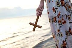 Menina cristã da senhora que guarda uma cruz santamente em sua mão e a posição na praia durante o tempo da noite do por do sol fotos de stock