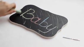 A menina cruza a inscrição na placa com o bebê da palavra, infertilidade, teste de gravidez, mão video estoque