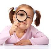 A menina curiosa está olhando através da lupa fotografia de stock