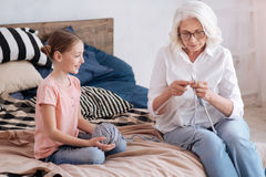 Menina curiosa positiva que olha sua avó imagens de stock royalty free
