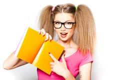Menina Curly com vidros que aponta no livro aberto foto de stock royalty free