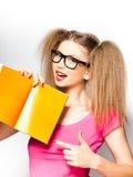 Menina Curly com vidros que aponta no livro aberto imagem de stock
