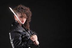Menina curly e espada da mulher Piercing Imagens de Stock