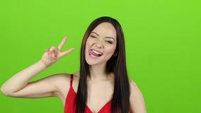 A menina da aparência asiática tem o divertimento e faz careta diferentes Tela verde Movimento lento vídeos de arquivo