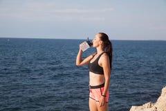 A menina da aptidão bebe o treinamento do esporte de água Fotos de Stock