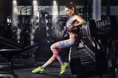 Menina da aptidão com a toalha e o abanador que relaxam no gym imagem de stock royalty free