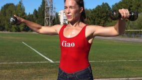 Menina da aptidão que exercita com pesos em Sunny Summer Day video estoque