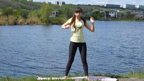 Menina da aptidão que exercita fora ao lado do rio que faz o exercício da ocupa em paisagem surpreendente da natureza Jovem mulhe video estoque