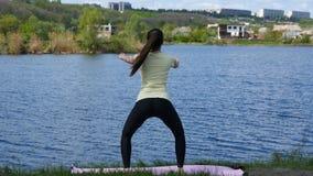 Menina da aptidão que exercita fora ao lado do rio que faz o exercício da ocupa em paisagem surpreendente da natureza Jovem mulhe filme
