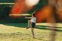 menina da aptidão que faz esticando exercícios exterior na luz do sol fotos de stock royalty free