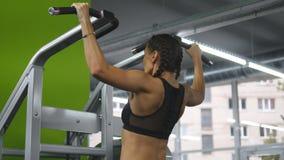 A menina da aptidão que faz a tração levanta no gym Jovem mulher que faz exercícios na barra horizontal Exercício de Bodyfitness  filme