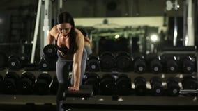 Menina da aptidão que levanta no banco no gym levanta o peso vídeos de arquivo