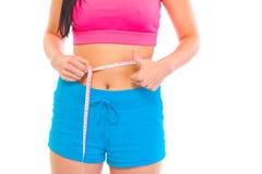 Menina da aptidão que mede sua cintura. Close-up. Imagens de Stock Royalty Free