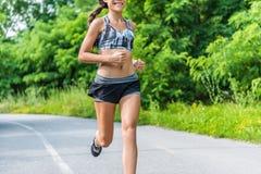 Menina da aptidão que corre no parque natural exterior do verão Fotografia de Stock Royalty Free