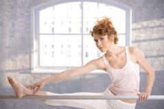 Menina da bailarina que estica pela barra no estúdio fotografia de stock royalty free