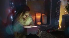 A menina da beleza abre a caixa de presente do Natal com luzes do milagre Mulher surpreendida que obtém o presente mágico vídeos de arquivo