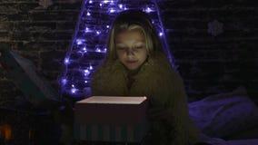A menina da beleza abre a caixa de presente do Natal com luzes do milagre Mulher surpreendida que obtém o presente mágico filme
