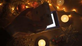 A menina da beleza abre a caixa de presente do Natal com luzes do milagre Mulher surpreendida que obtém o presente mágico video estoque