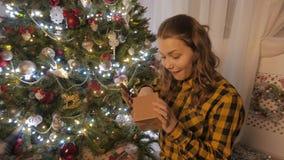 A menina da beleza abre a caixa de presente do Natal 4k UHD vídeos de arquivo